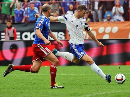Bosnia and Herzegovina's Edin Dzeko (R) vies with Liechtenstein's Mario Frick (L) on his way to score a goal during a friendly international football match, in Tuzla, on September 4, 2014. Bosnian national team had won the match 3:0. AFP PHOTO ELVIS BARUKCIC