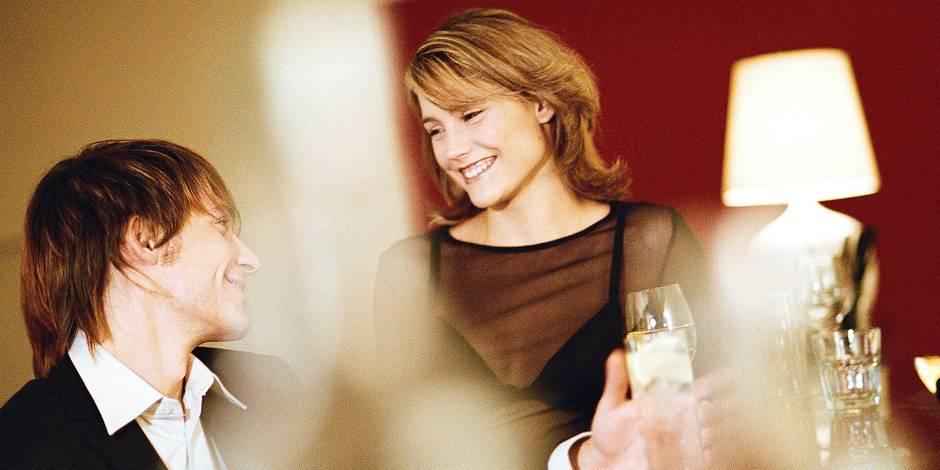 Young man and woman at bar, smiling